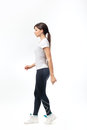Full length of a young woman walking over white background Royalty Free Stock Photo