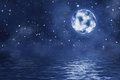 Full moon with bright shining stars and nebula over water with waves