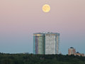 Full moon in evening sky over urban houses Royalty Free Stock Photo