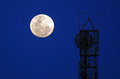 stock image of  Full moon rise against silhouettes of television and radio antenna
