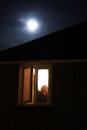 Full moon woman closing curtain on the window Royalty Free Stock Images