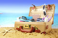 Full open suitcase on tropical beach background Stock Photography