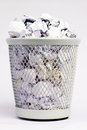 Full paper bin silver coloured metal of white pieces rolled into balls Stock Photo