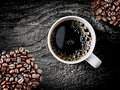 Full roast coffee beans with freshly brewed coffee piled on a rough rustic wooden surface a cup of espresso frothy bubbles Stock Photo