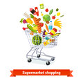 Full shopping grocery cart exploding with goods