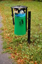 Full trash bin green at a park in poznan poland Stock Photo