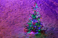 Fully decorated illuminated Christmas tree with ornaments on snowy spruce branches Royalty Free Stock Photo