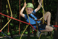 Fun in adventure park young boy climbing a rope way an having Stock Photography