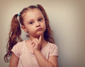 Fun annoyed kid girl thinking and looking serious about closeup vintage portrait Stock Images