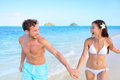 Fun on beach couple in a happy relationship running together hawaiian during holidays travel vacation mixed race asian Royalty Free Stock Images