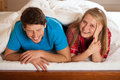 Fun in bed a couple laughing and having while lying Stock Images