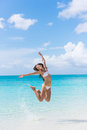 Fun bikini woman jumping on beach splashing water happy having of joy and happiness in perfect turquoise asian girl cheering Royalty Free Stock Photos