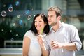Fun with bubble blower young couple play together outdoor in street Royalty Free Stock Photography