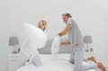 Fun couple having a pillow fight at home in bedroom Stock Photo