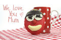 Fun cute childrens handmade cookie with candy face and red polka dot cup of tea or coffee for Mothers Day Royalty Free Stock Photo