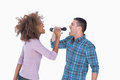Fun duo singing to each other at karaoke on white background Stock Photos
