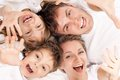 Fun family portrait of a cheerful having together lying on a bed at home top view Royalty Free Stock Images
