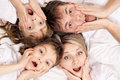 Fun family portrait of a surprised having together lying on a bed at home top view Royalty Free Stock Image