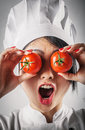 Fun goofy chef with tomato eyes young female asian in her white toque and uniform holding two juicy ripe red over her while Stock Photo