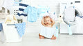 Fun happy baby boy  to wash clothes and laughs in laundry Royalty Free Stock Photo