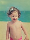 Fun happy baby girl looking on beach background vintage portrait Royalty Free Stock Image