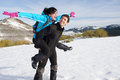 Fun hiking couple in winter playful having on trip to mountain man and women enjoying freedom playing around and laughing on snow Royalty Free Stock Image