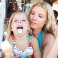Fun little girl eating ice cream with mom Stock Photo