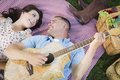 Fun mixed race couple playing guitar and singing happy on picnic blanket at the park songs Stock Image