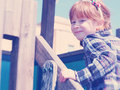 Fun on the playground five six year old little girl with red hair turning towards viewer and smiling Stock Images