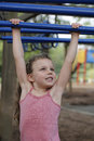 Fun at the playground little girl plays on monkey bars a hangs from while playing in park Royalty Free Stock Images