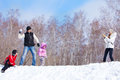 Fun playing snowball family parents with children walking at winter park Stock Images