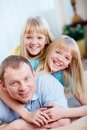 Fun portrait of happy men with twin daughters looking at camera Stock Image