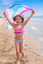 Fun summer vacations little girls playing with a rainbow cloth at the beach Stock Photography