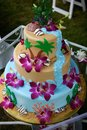 Fun tropical beach wedding cake three tiered themed with shells and palm trees and real purple flowers with a waterfall and brown Royalty Free Stock Images