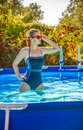 Active woman in swimming pool looking aside in sunglasses