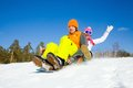 Fun winter holiday couple of young people slide downhill together on mountain Stock Photography