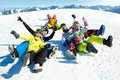 Fun winter holiday group of funny friends slide downhill together on mountain Stock Images