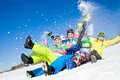 Fun winter holiday group of funny friends slide downhill together on mountain Royalty Free Stock Photos