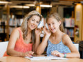 That is fun wth mum a teenage girl with headphones sitting in a library with her Stock Photography