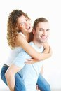 Fun young happy men giving piggyback to his girlfriend Stock Images