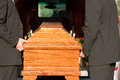 Funeral with casket carried by coffin bearer dolor on a cemetery the Stock Photography