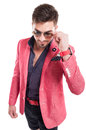 Funky fashion man wearing pink jacket shorts and sunglasses looking down Stock Images