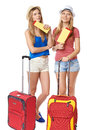 Funky girls travelers two contemplating in shorts and straw hats standing with travel bag holding tickets looking away isolated on Royalty Free Stock Photos
