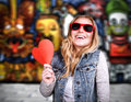 Funky teen girl in love having fun outdoors holding hands red heart as symbol of adolescents affection urban lifestyle stylish Stock Photography