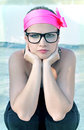 Funky woman wearing a neon pink headband and geek glasses. Royalty Free Stock Photo