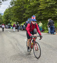 Funny amateur cyclist le markstein france july fanny wearing a us flag hat climbing the road to the mountain pass le markstein Stock Photo
