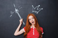Funny amazed woman with drawn crown standing over blackboard background Royalty Free Stock Photo