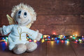 Funny angel and bright lights garlands on wooden boards