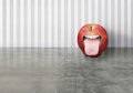Funny apple artistic creation of a red with an opened human mouth that sticking out his tongue Royalty Free Stock Image