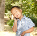 Funny asian boy with a mobile phone in a park Royalty Free Stock Photo